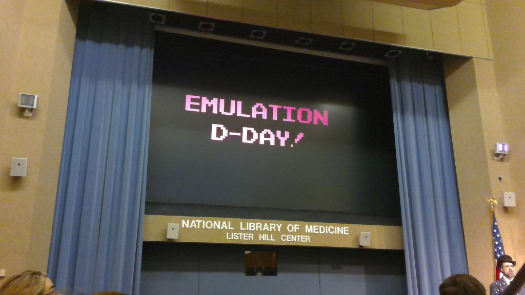 "Jason Scott presenting at the National Digital Stewardship Residency 2016 Symposium. The presentation screen shows the phrase ""Emulation D-Day!"""