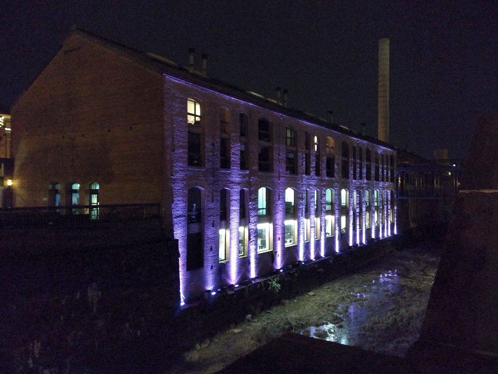 A building at nighttime. It is located along an overgrown canal. The side of the building is lit with purple columns of light. In the distance, a white smokestack is visible.