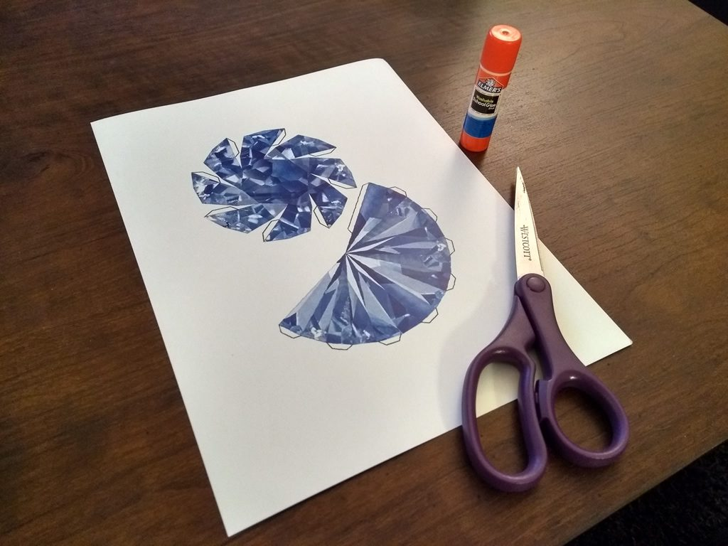 A printout of a flat model of a blue sapphire, sitting on a table. Next to the paper are a pair of scissors and a glue stick.