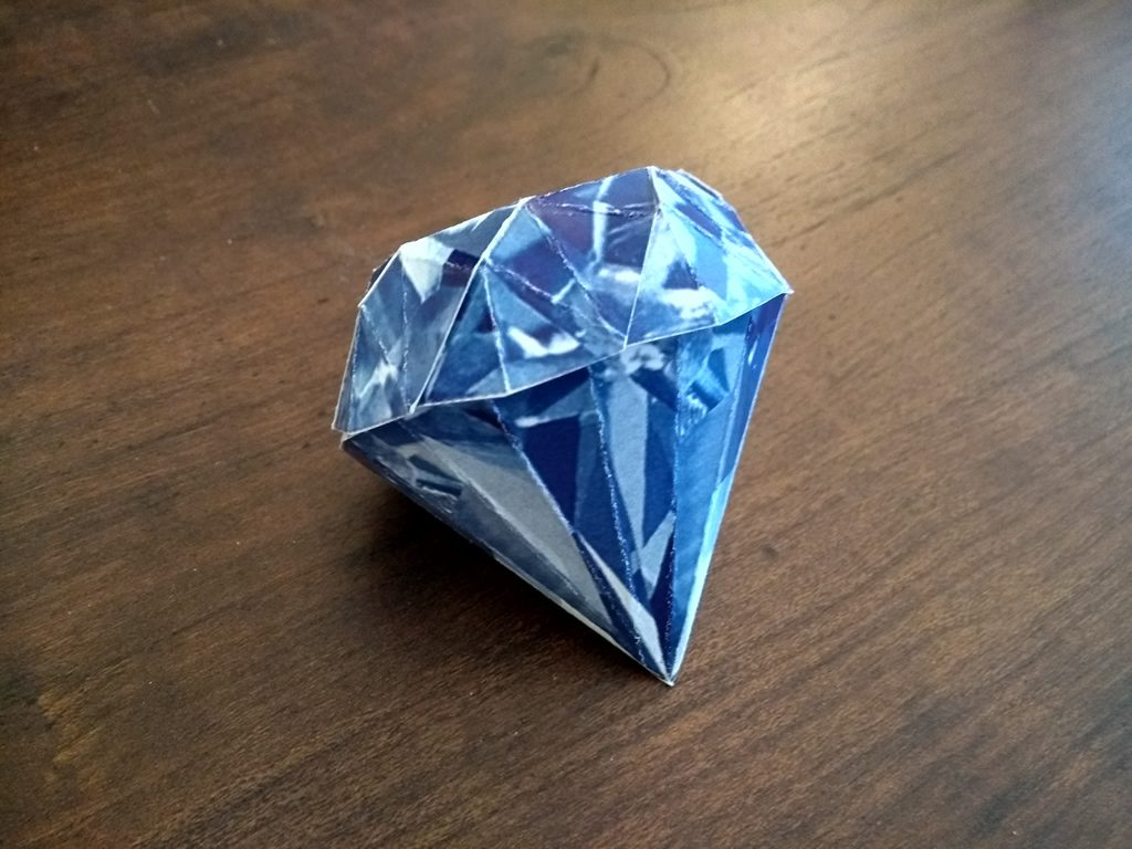 A 3D paper model of a blue sapphire on top of a table. The folds are slightly crooked and rough because I'm not great at papercraft.