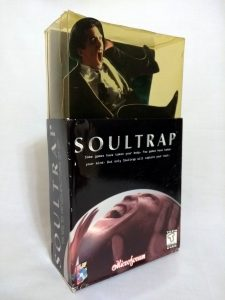 The packaging for SoulTrap. The front of the box has an illustration of a man, either laughing or screaming, trapped in a sphere and pushing his hands against the inside. On top of the box, there is a three-dimensional cutout of another man in a suit screaming; he is trapped in a yellow-tinted plastic enclosure.