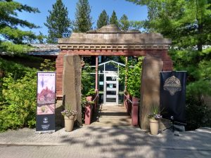 The entrance to Cyan Worlds headquarters in Mead, WA. A red stone arch stands in front of a small walkway bridge to the front door. On other side of the entrance are banners for the games Obduction and Firmament, with conifer trees further to the sides.
