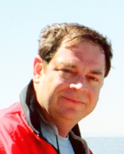 A photo of John Hiles wearing a red windbreaker.