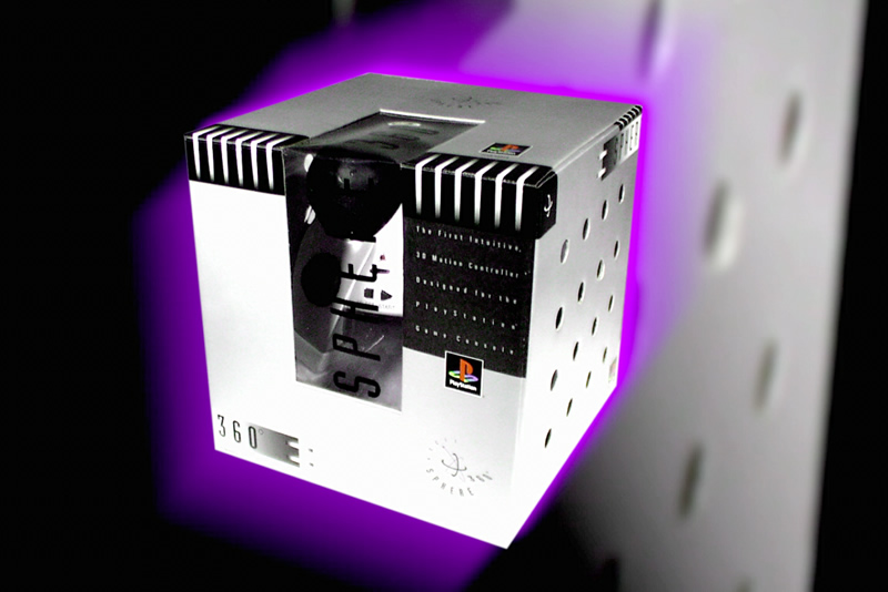 The box for the Asciiware Sphere 360 PlayStation controller. The controller itself is barely visible. The box is a bizarre steel-colored cube with air holes in the side, giving it an industrial appearance. In the picture, the box is glowing purple.