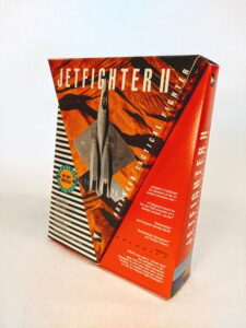 The box for JetFighter II: Advanced Tactical Fighter. There's a large triangular section protruding about half an inch out of the face of the box with a picture of a jet fighter on it. The other sections of the box are either solid red or black-and-white striped.