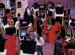 The crowded show floor at E3 1995. A large number of game booths are visible, most prominently Electronic Arts and PlayStation.