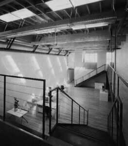 A large loft-style room with an exposed ceiling. The room is mostly sparse apart from a few desks with computers. The room is two stories tall, and the vantage point of the photo is from a catwalk on the edge of the room, suggesting the building's original purpose as a machine shop.