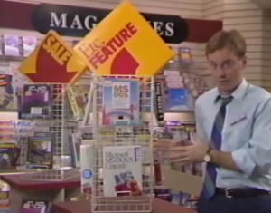"""A Software Etc. employee standing in front of a display of boxed software. There are large arrow signs labeled """"Sale"""" and """"Etc. Feature"""" pointed at copies of the MS-DOS operating system sitting on the racks."""