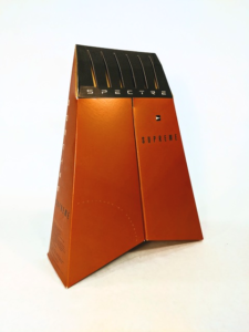 The box for Spectre Supreme. It is a tapered, bronze-colored pyramid, with the bottom of the box slightly folded inward to create a chevron shape.